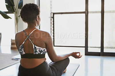 Buy stock photo Rearview shot of a young woman meditating at home