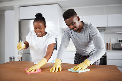 Buy stock photo Shot of a young couple cleaning the kitchen counter at home