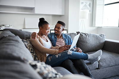 Buy stock photo Shot of a young couple using a laptop together on a sofa at home