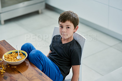 Buy stock photo Shot of a cute young boy having cereal for breakfast at home