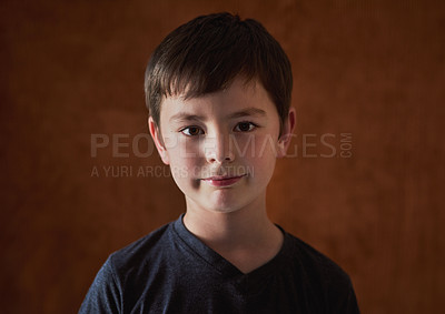 Buy stock photo Portrait of an adorable young boy standing against a brown background
