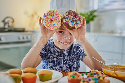 Buy stock photo Shot of an adorable little boy making cupcakes and doughnuts at home