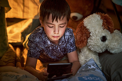 Buy stock photo Shot of an adorable little boy using a digital tablet under a blanket fort at night in his bedroom