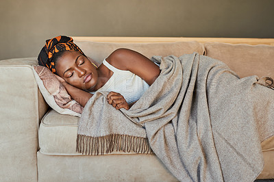 Buy stock photo Shot of a young woman having a nap on the sofa at home