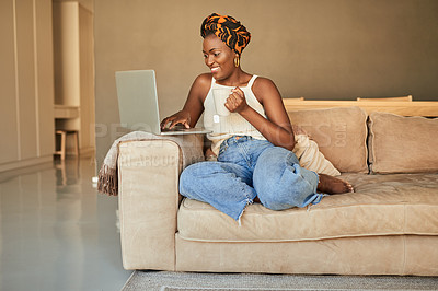 Buy stock photo Shot of a young woman having a warm beverage and using a laptop on the sofa at home