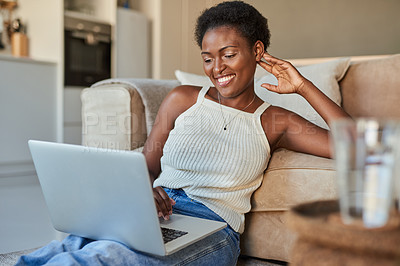 Buy stock photo Shot of a young woman using a laptop during a relaxing day at home