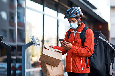 Buy stock photo Shot of a masked man using his cellphone while doing a food delivery