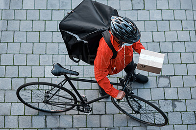 Buy stock photo Shot of a masked man out with his bicycle to do a delivery