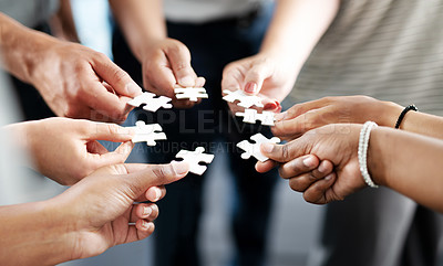 Buy stock photo Closeup shot of a group of unrecognisable businesspeople holding puzzle pieces together