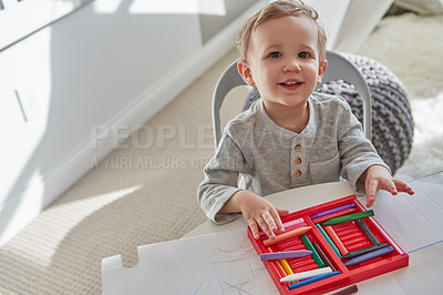Buy stock photo Cropped shot of a little boy playing with his crayons at home