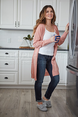 Buy stock photo Shot of a beautiful young woman having coffee while standing by the refrigerator in the kitchen at home