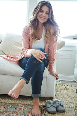 Buy stock photo Portrait of a beautiful young woman relaxing on a sofa at home