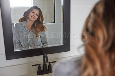 Buy stock photo Shot of a young woman admiring herself in the bathroom mirror at home