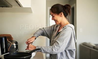 Buy stock photo Cropped shot of a young woman cooking in the kitchen at home