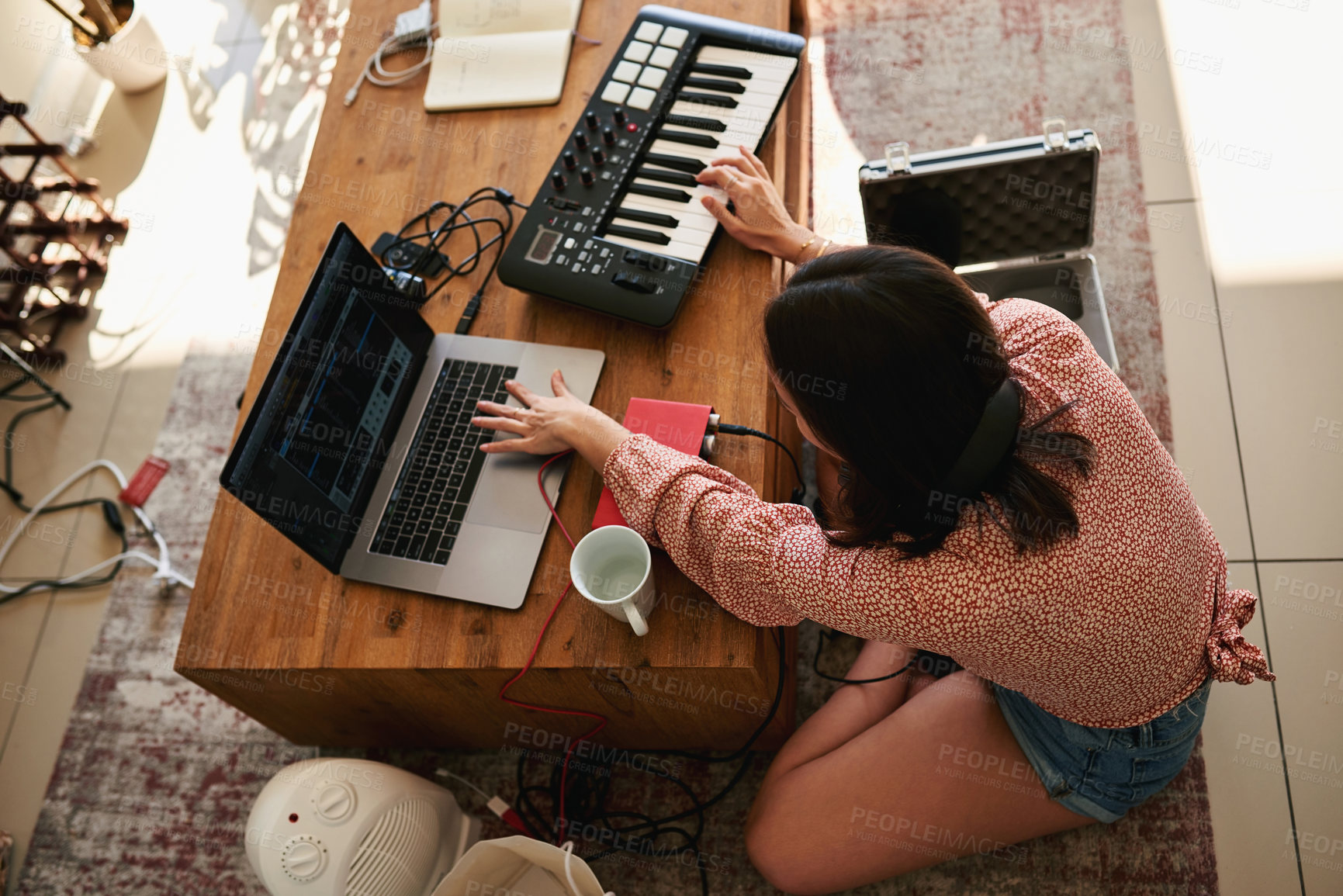 Buy stock photo Shot of a young woman using her laptop while making music at home