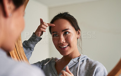 Buy stock photo Cropped shot of a young woman looking at her face in the mirror at home