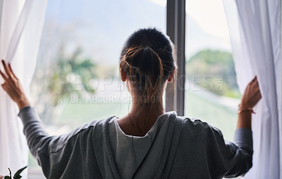 Buy stock photo Cropped shot of a young woman looking out the window at home