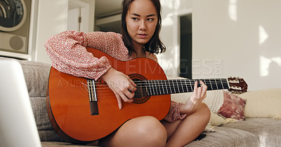Buy stock photo Shot of a young woman using a laptop while playing a guitar on the sofa at home
