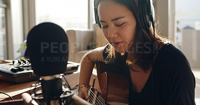 Buy stock photo Shot of a young woman recording herself singing and playing the guitar at home