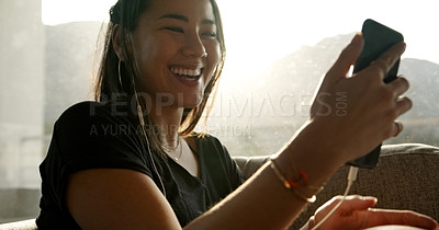 Buy stock photo Shot of a young woman using a smartphone to make a video call at home