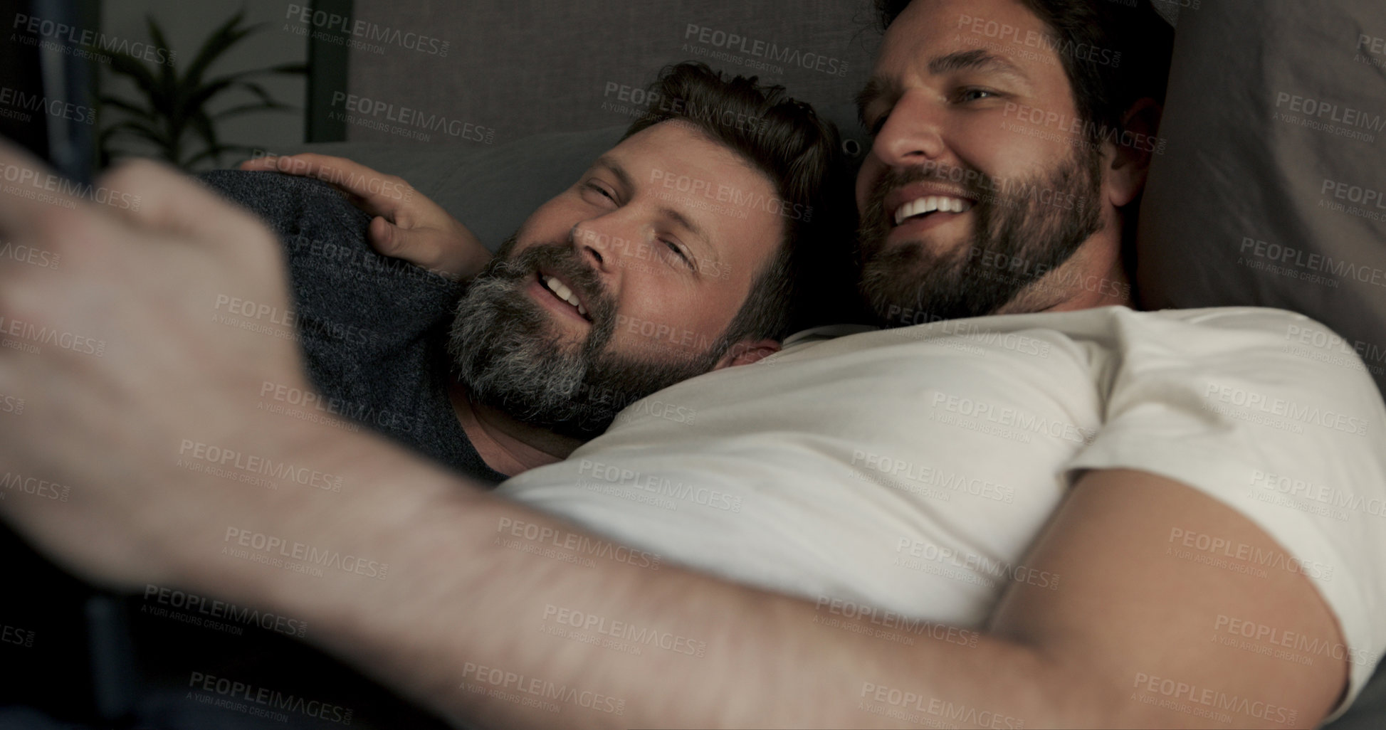 Buy stock photo Cropped shot of a handsome mature couple watching series on their tablet while relaxing in bed