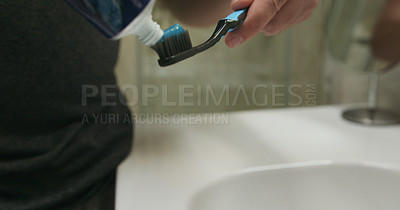 Buy stock photo Cropped shot of an unrecognizable man applying toothpaste to his toothbrush in the bathroom at home