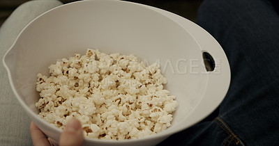 Buy stock photo Shot of an unrecognisable man having popcorn while watching tv at home