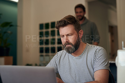 Buy stock photo Shot of a mature man using a laptop while working at home with his husband in the background