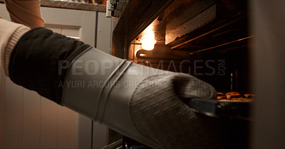 Buy stock photo Cropped shot of an unrecognisable woman removing her cookies from the oven