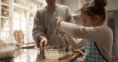 Buy stock photo Cropped shot of a little girl and her mother bonding while baking at home