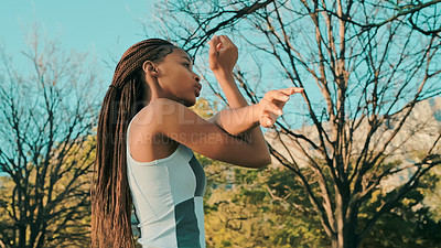 Buy stock photo Shot of a young woman stretching while out at the park