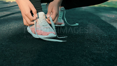 Buy stock photo Shot of a woman tying her shoelaces while out for a workout at the park