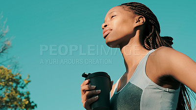 Buy stock photo Shot of a young woman enjoying a beverage while out exercising