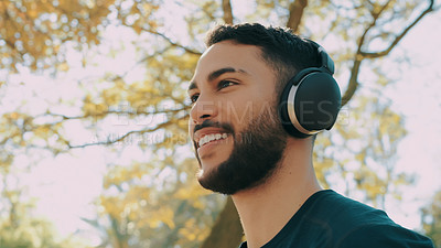 Buy stock photo Shot of a young man listening to music through his headphones while out at the park