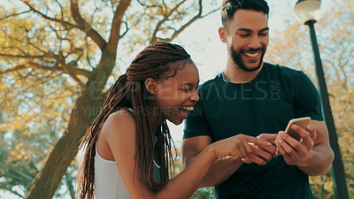 Buy stock photo Shot of a young couple discussing something on a cellphone while out at the park