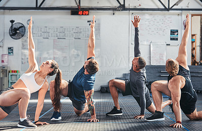 Buy stock photo Cropped shot of a group of young athletes going through their warmup routine in the gym