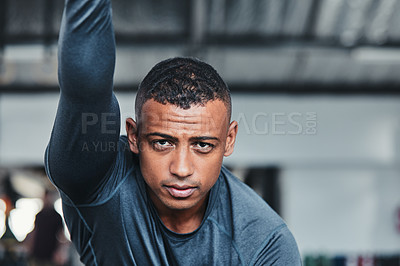 Buy stock photo Cropped portrait of a handsome young male athlete going through his warmup routine in the gym