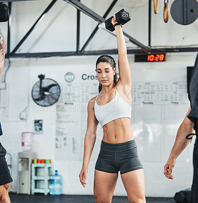Buy stock photo Cropped shot of an attractive young female athlete working out with a dumbbell in the gym