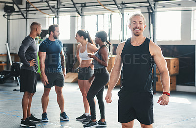 Buy stock photo Cropped portrait of a handsome young male athlete standing in the gym with other gym-goers in the background