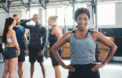 Buy stock photo Cropped portrait of an attractive young female athlete standing with her hands on her hips in the gym with other gym-goers in the background