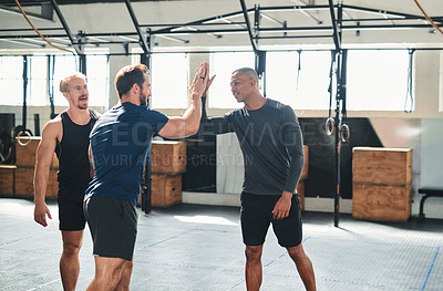 Buy stock photo Cropped shot of two handsome young male athletes high-fiving during a workout in the gym