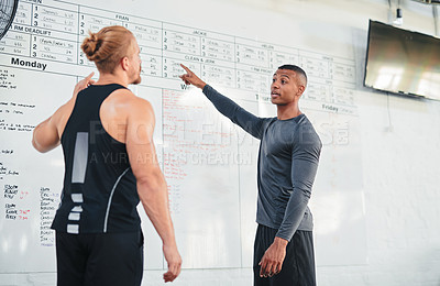 Buy stock photo Cropped shot of two handsome young male athletes looking at the workout schedule in the gym