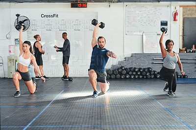 Buy stock photo Shot of a group of young athletes in an exercise class at the gym