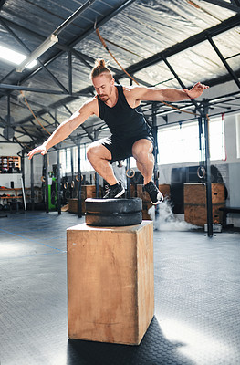 Buy stock photo Shot of a fit young man doing box jumps at the gym