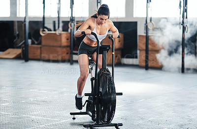 Buy stock photo Shot of a young woman doing cardio at the gym