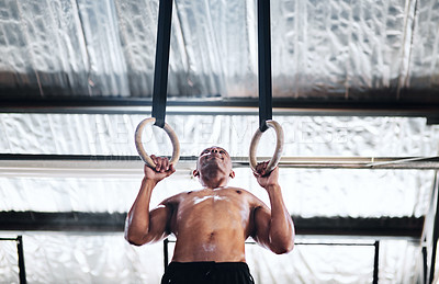 Buy stock photo Shot of a man working out with gymnastic rings