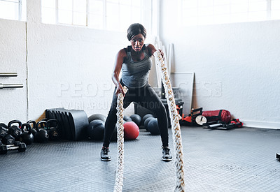 Buy stock photo Shot of a fit young woman working out with battle ropes at the gym