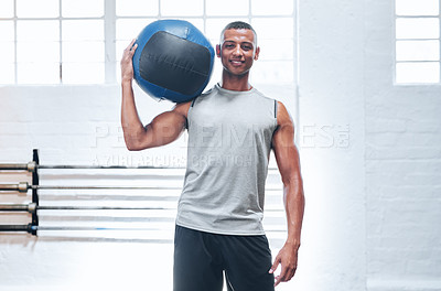 Buy stock photo Portrait of a muscular young man holding up a medicine ball