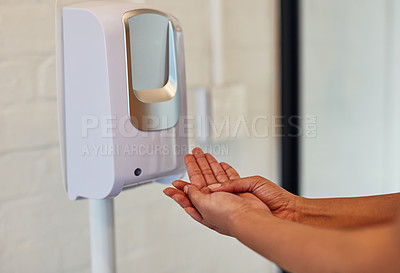 Buy stock photo Cropped shot of a woman using a hand sanitiser dispenser in a bathroom