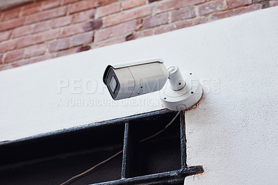 Buy stock photo Low angle shot of a security camera mounted on a building wall outside